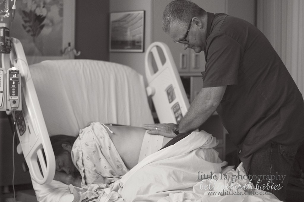 father supporting mother while birthing on knees in hospital